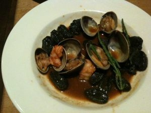 Squid ink gnocchi with atlantic prawns, clams and samphire